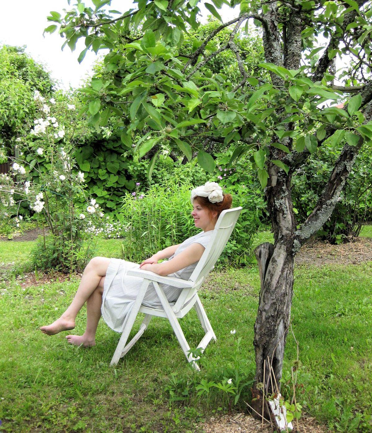 Tyttö omenapuun alla valkoisessa mekossa.