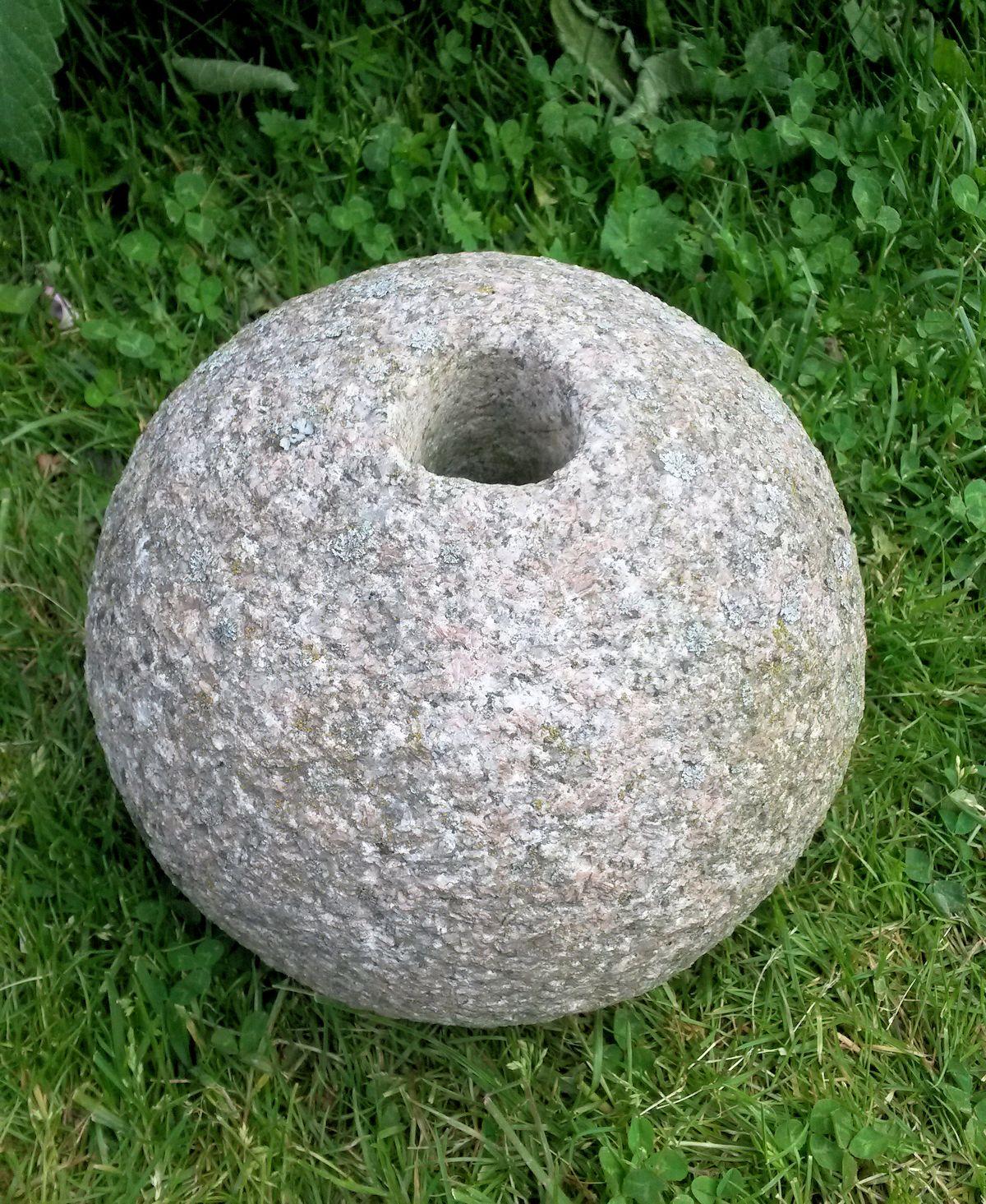 Kivipallo reikä keskellä.