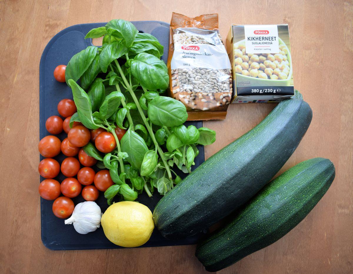 Kesäkurpitsaspagetin raaka-aineet: kesäkurpitsaa, kirsikkatomaatteja, basilikaa, auringonkikansiemeniä, kikherneitä, valkosipulia ja sitruunanmehua. Lisäksi paistamiseen öljyä ja mausteeksi ainakin suolaa ja pippuria.