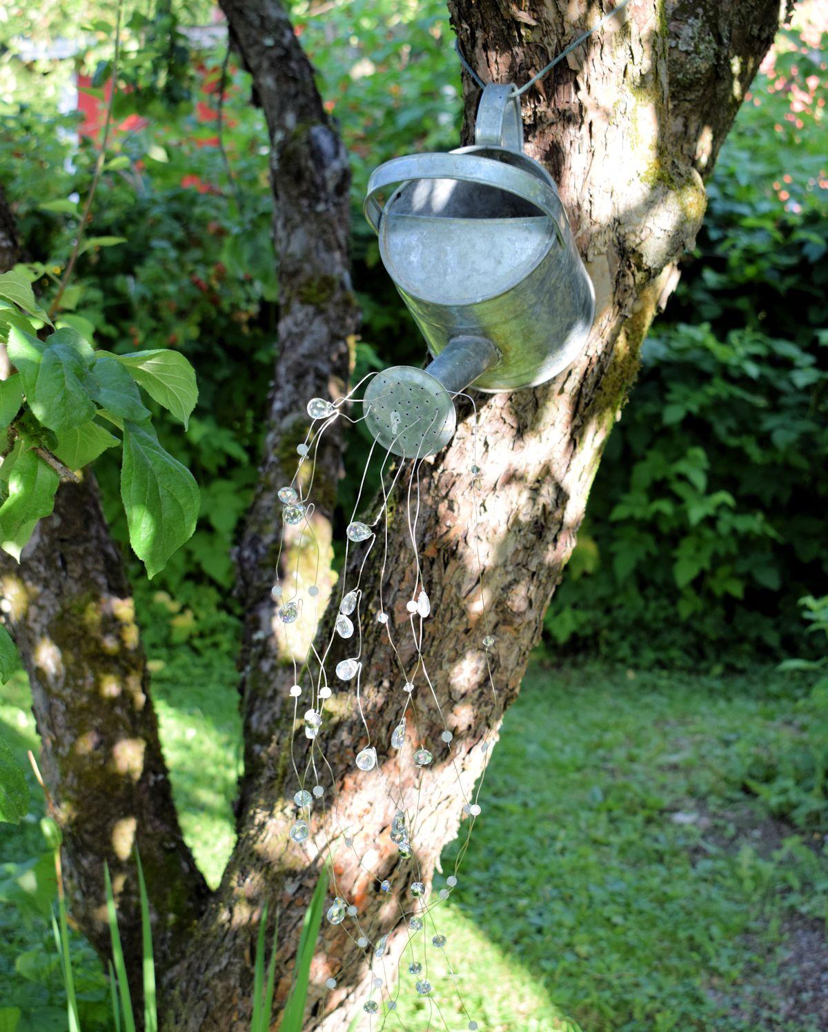 Sinkkinen kastelukannu omenapuussa.