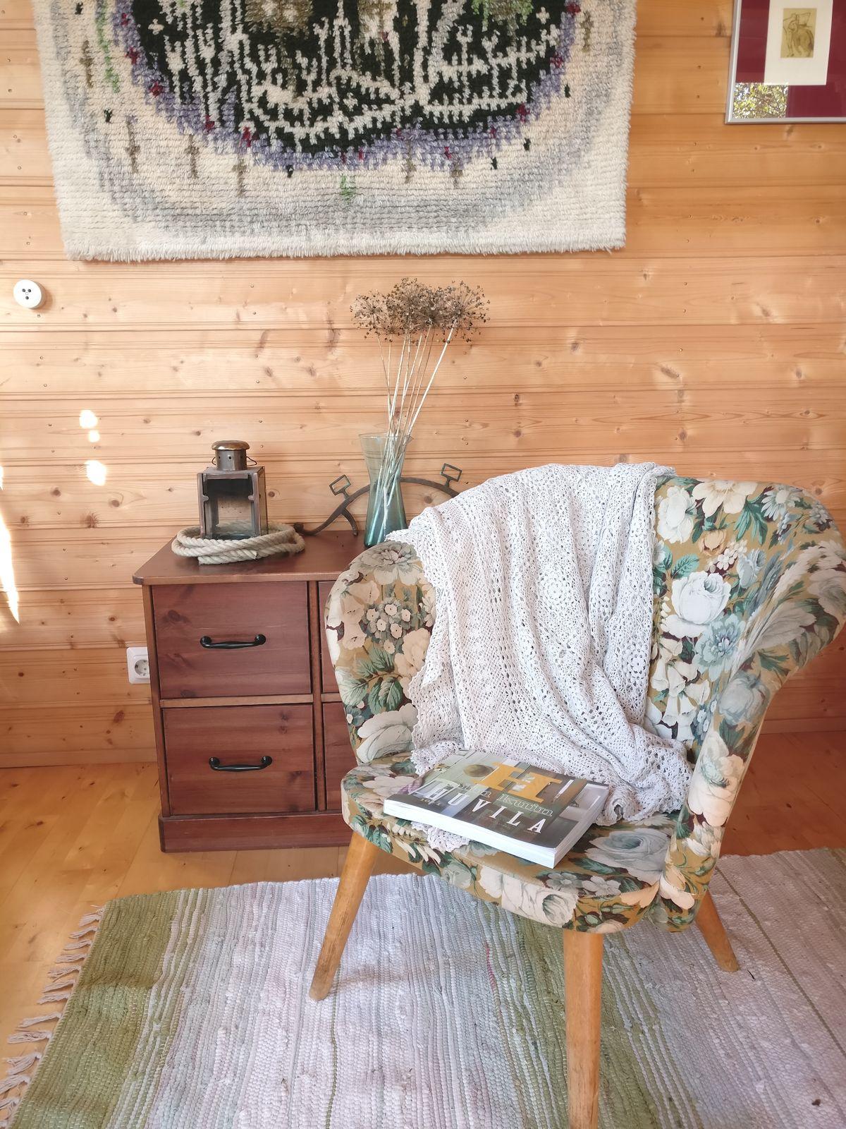 Pikkuinen nojatuoli kukallisella kankaalla.