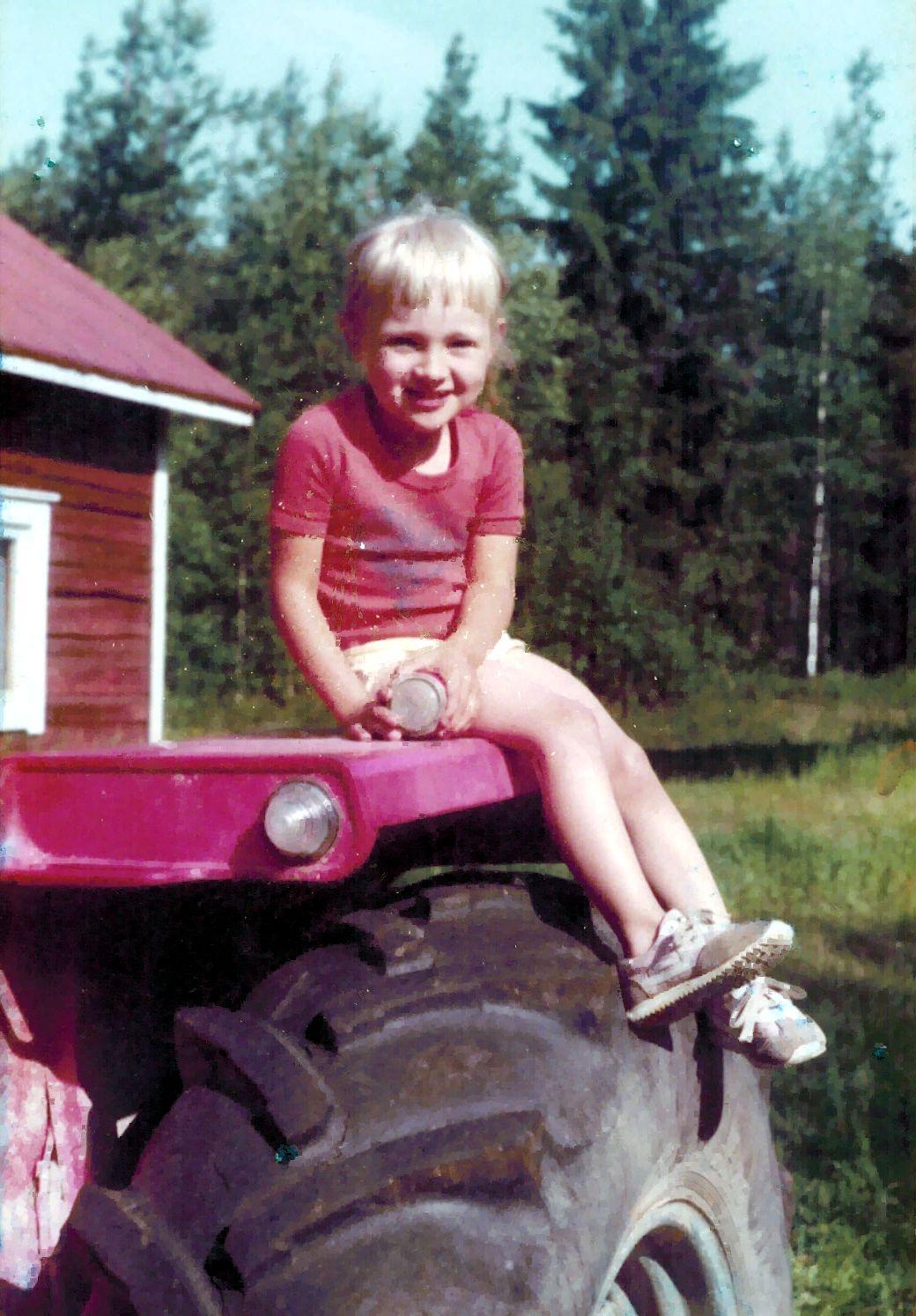 Pieni tyttö istuu traktorin renkaalla.
