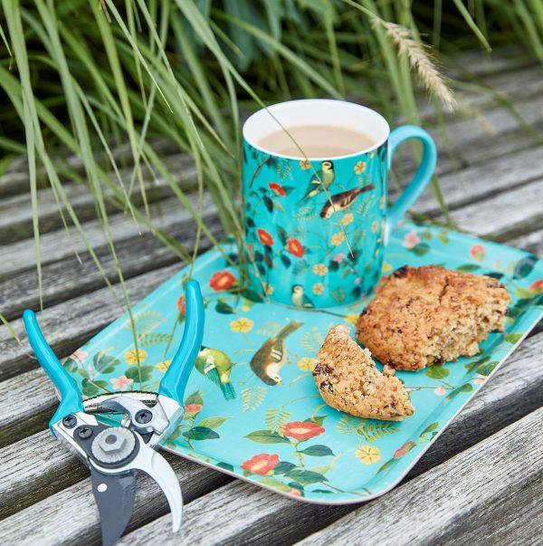 Pieni vaneritarjotin kahvikuppi ja puutarhasakset