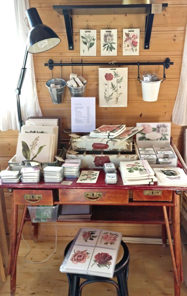 Sköna Ting kasvitaulut ja postikortit vanhan kirjoituspöydän päällä.