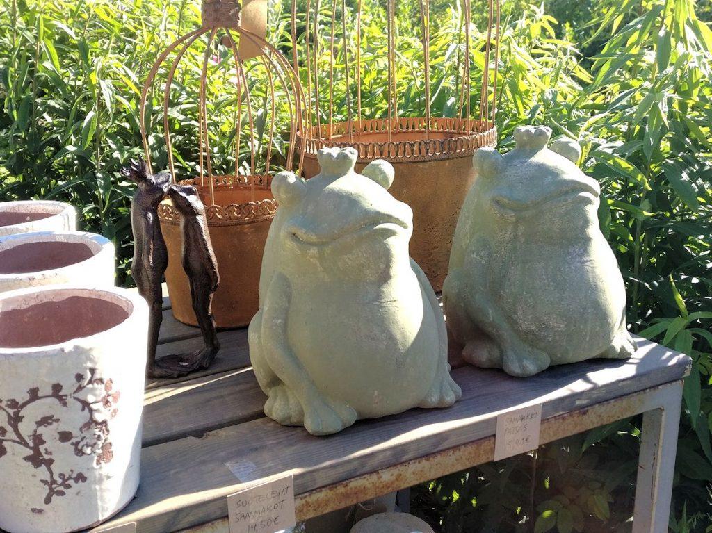 Miljögardenin puutarhakoristeita: patsaita, ruosteisia ruukkuja ja ruusuruukkuja.