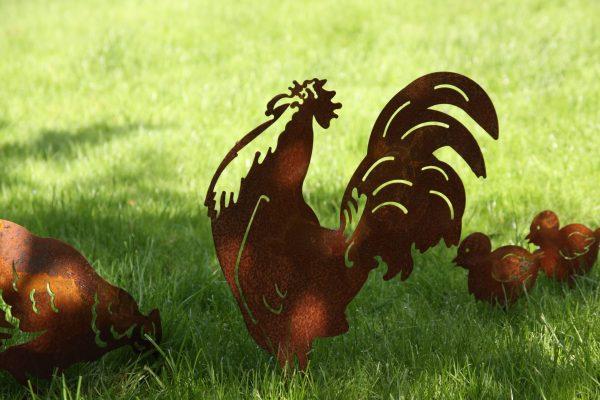 Ruosteiset kana kukko ja tipu puutarhakoristeet nurmikolla