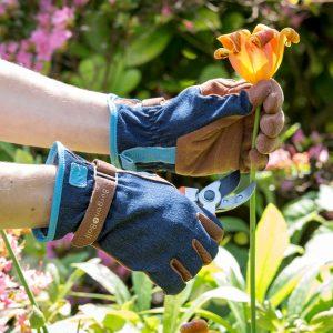 kukan leikkaus oksasaksilla farkkukankaasta tehdyt puutarhahanskat kädessä