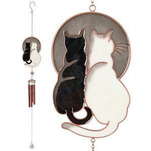 tuulikello istuva musta ja valkoinen kissa