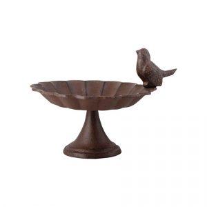 pieni ruosteen värinen jalallinen lintujen kylpyallas jonka reunalla pieni lintu