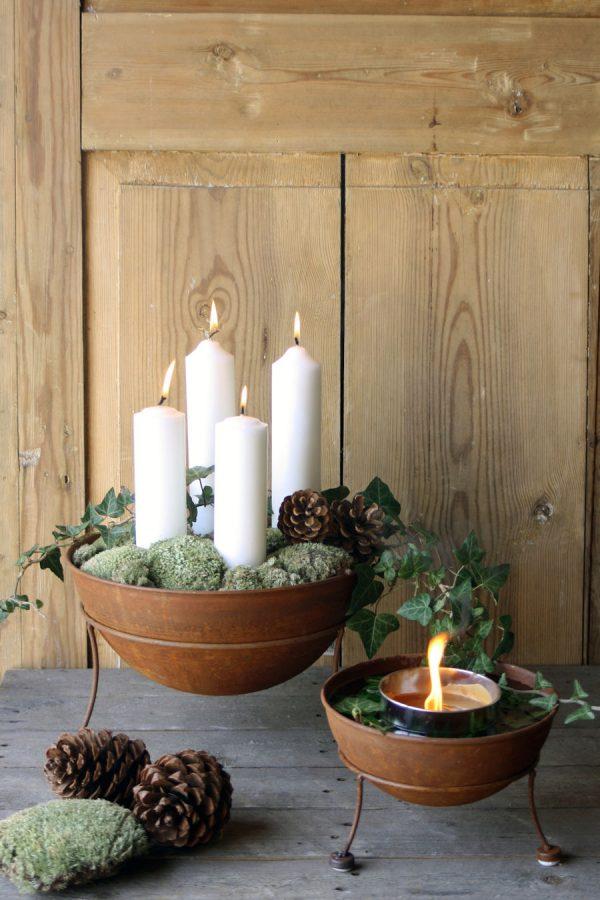 kaksi eri kokoista ruosteista kulhoa, joissa kynttilöitä